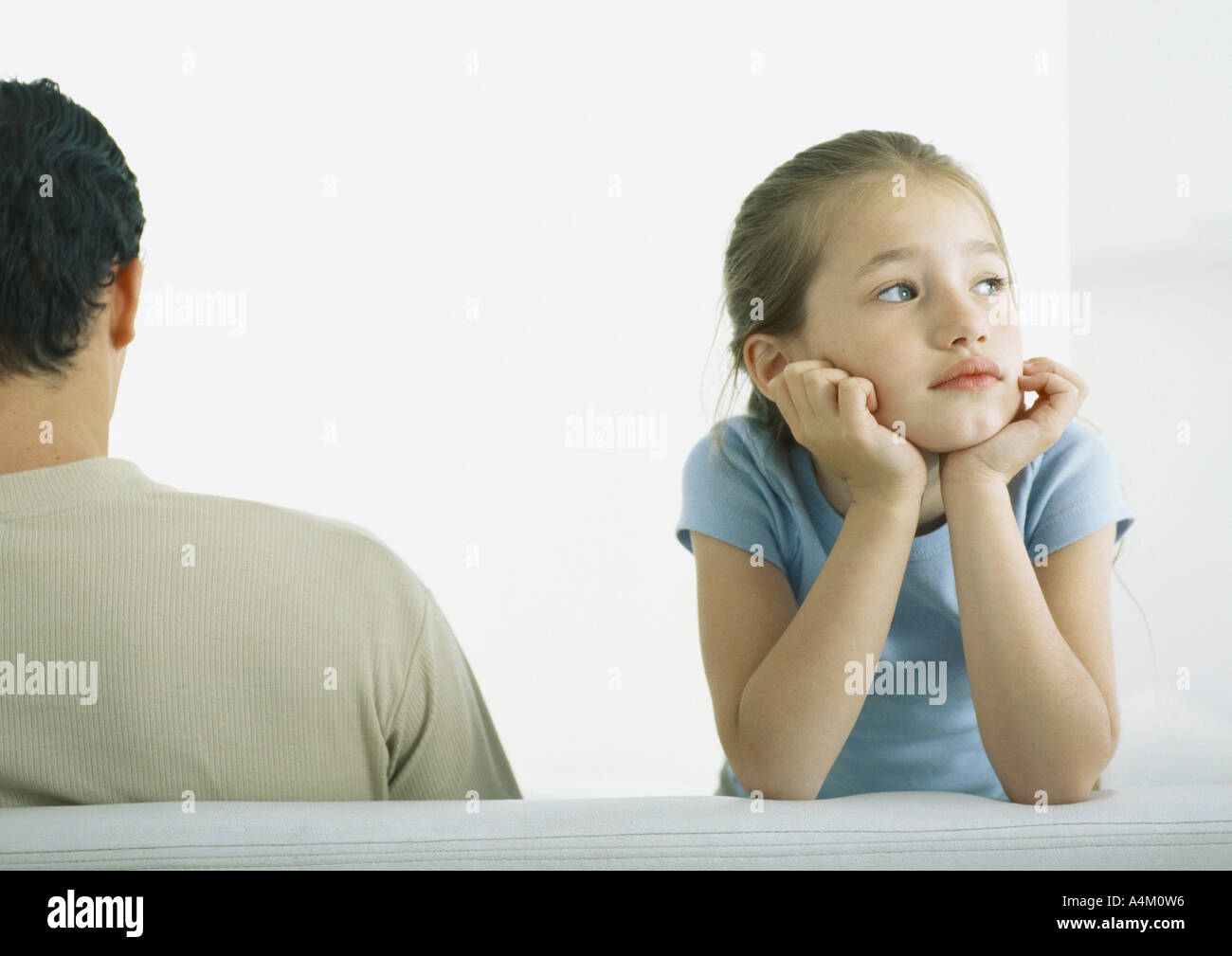 Girl holding head, leaning on elbows next to man, rear view - Stock Image