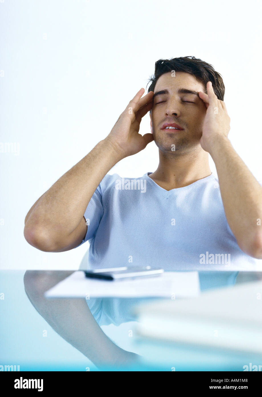 Man sitting at table, rubbing head - Stock Image