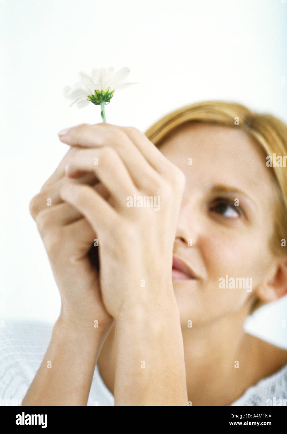 Woman holding up flower, looking at it - Stock Image