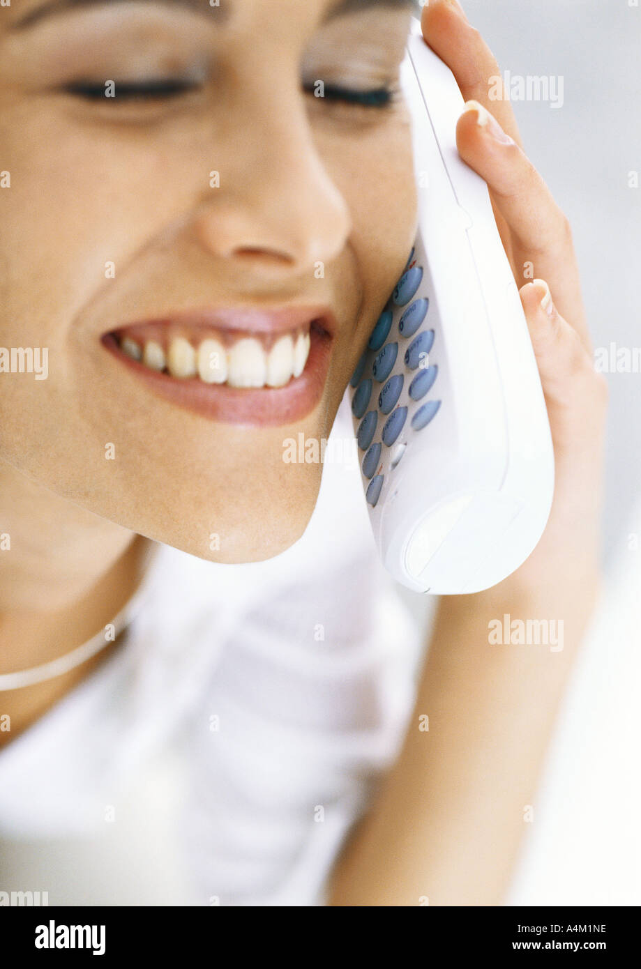 Woman talking on cordless phone with eyes closed, smiling - Stock Image