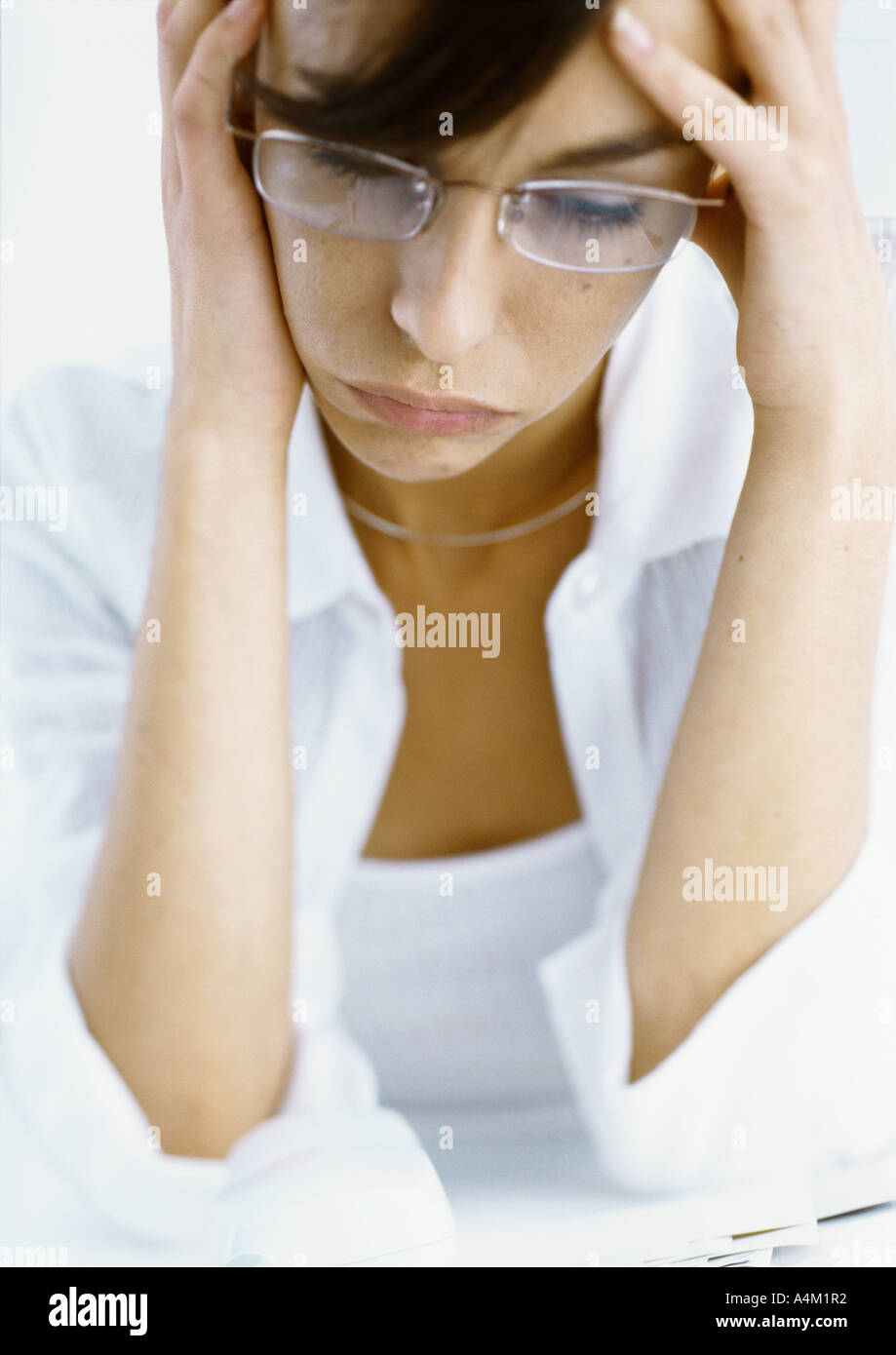 Woman holding head in hands, looking down, high angle view - Stock Image
