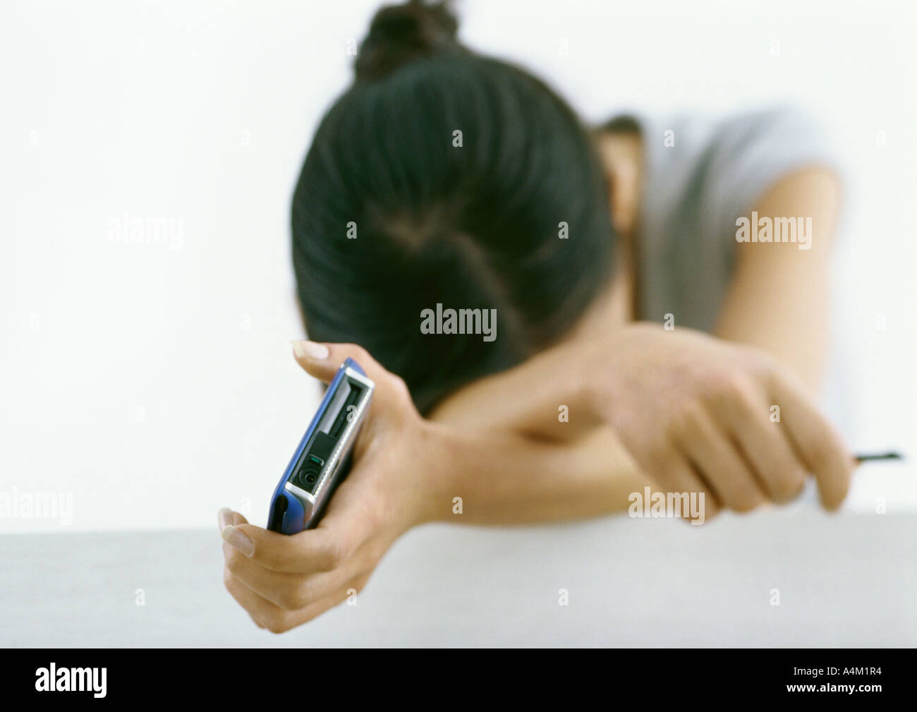 Woman holding electronic organizer, resting head on arms - Stock Image