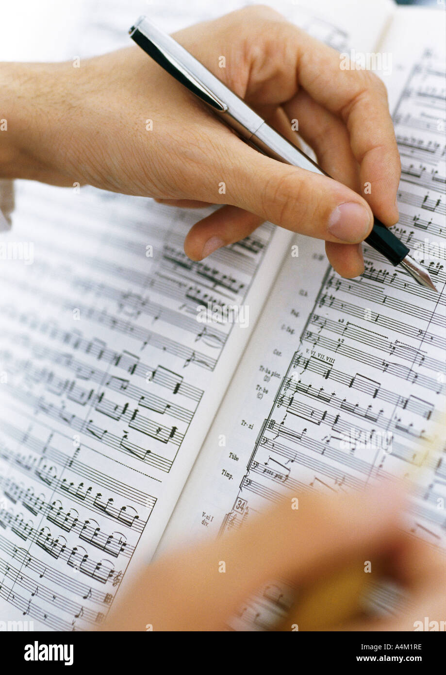 Hands writing on sheet music, close-up - Stock Image