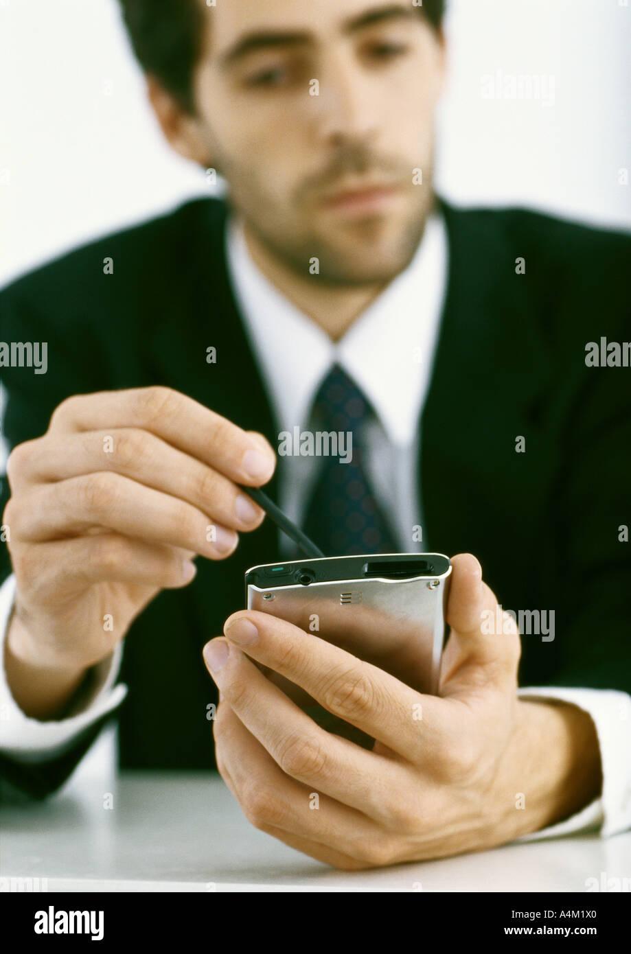 Businessman using electronic organizer - Stock Image