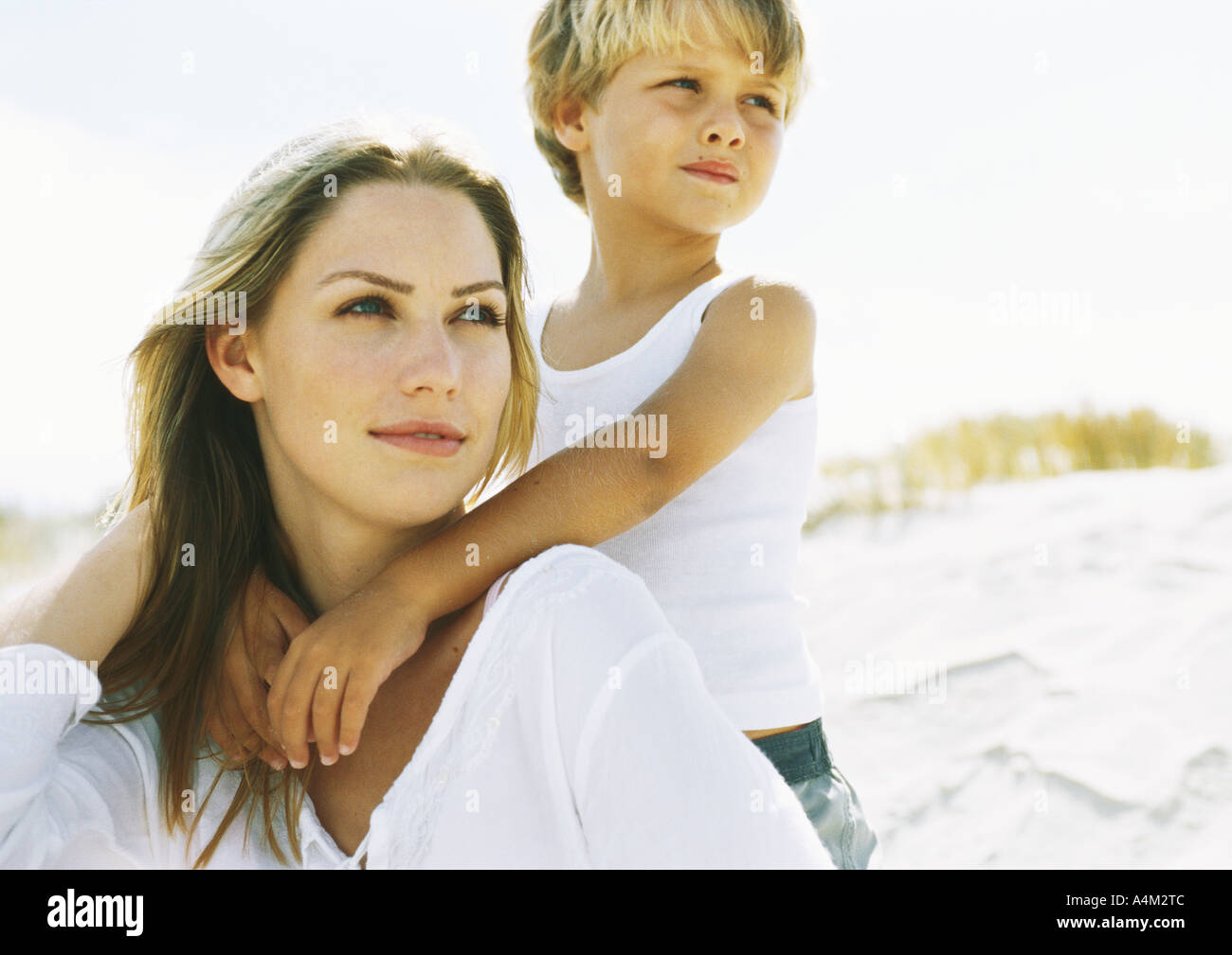 Boy standing behind seated mother on beach, portrait - Stock Image