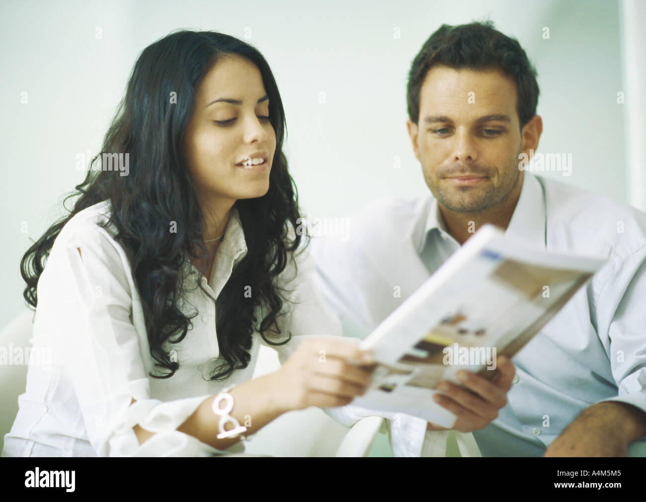 Young adults examining catalog - Stock Image