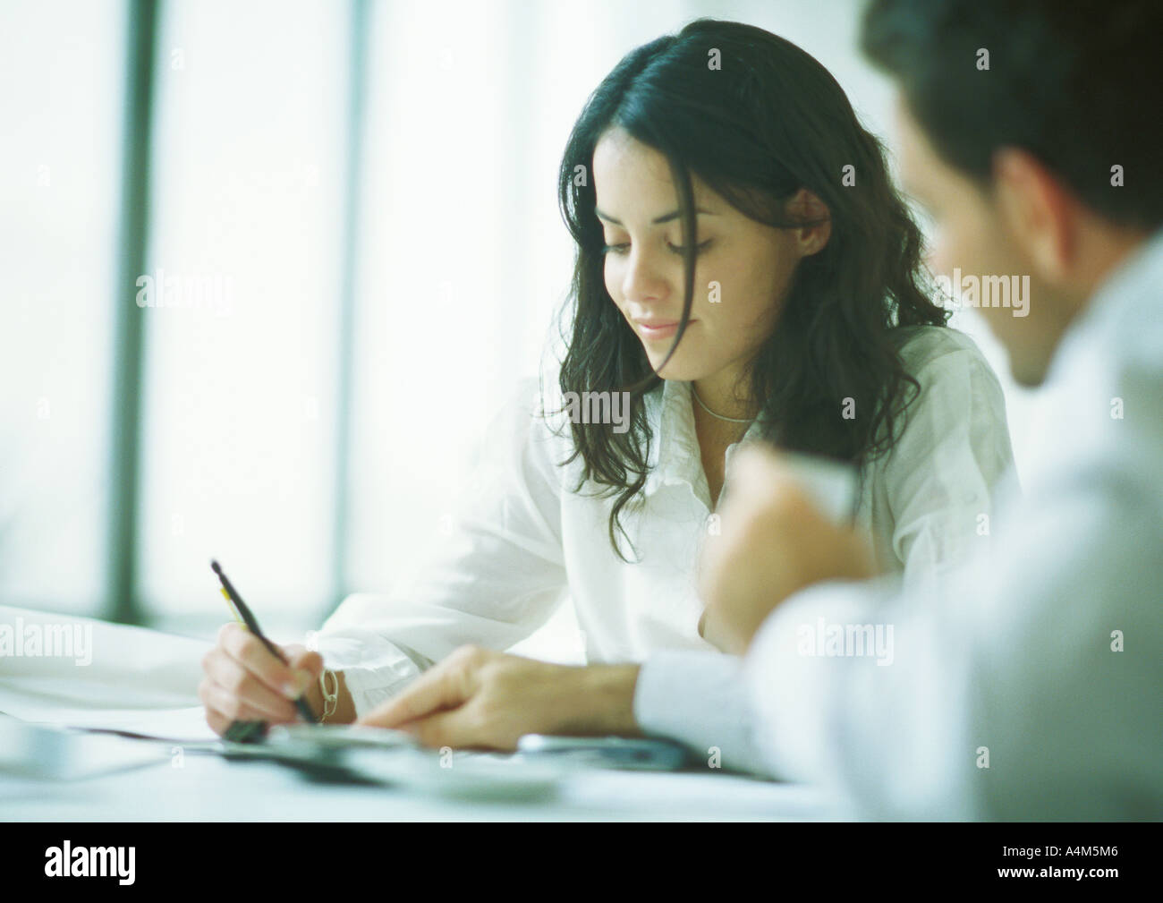 Young adults examining documents, woman holding pencil as man points - Stock Image