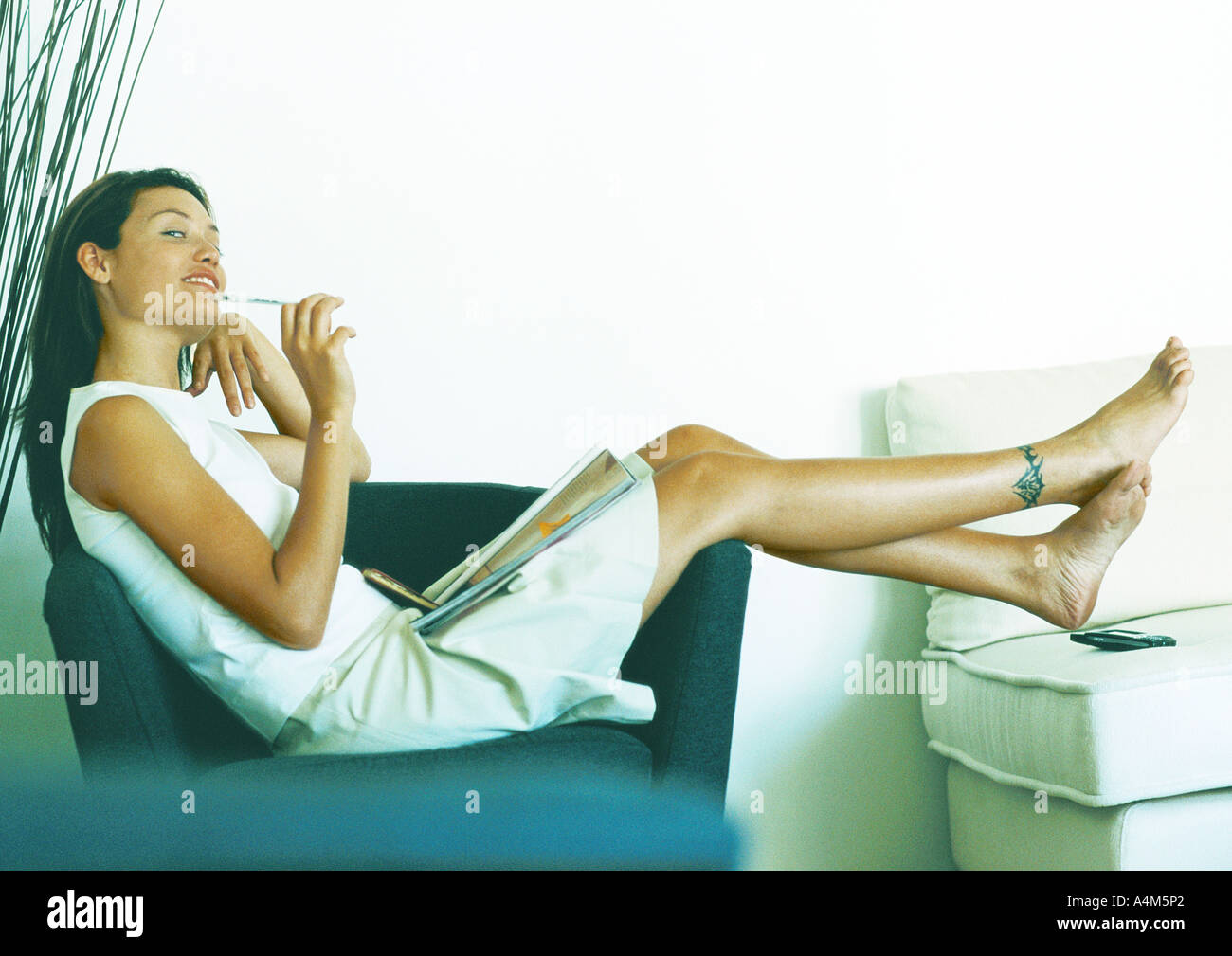 Woman sitting sideways on armchair, full length - Stock Image