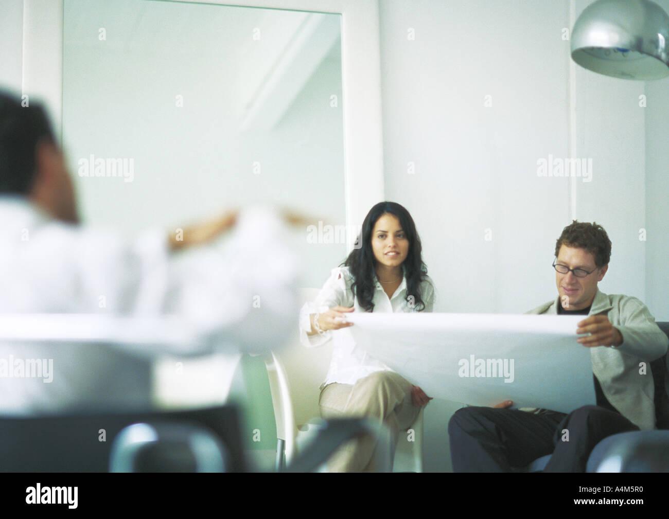 Young adults examining blueprints - Stock Image