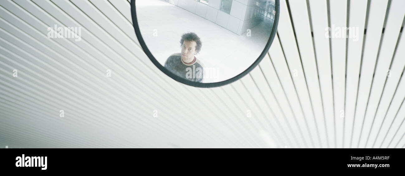 Young man's reflection in mirror - Stock Image
