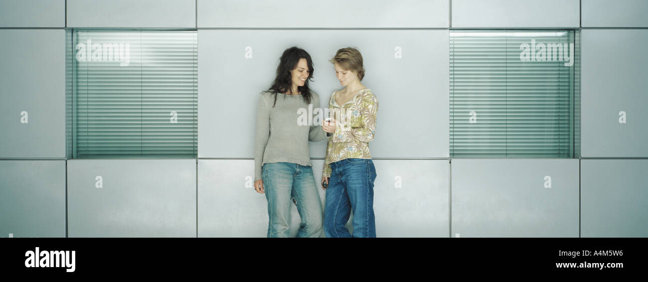 Two young women leaning against wall, together reading text message - Stock Image