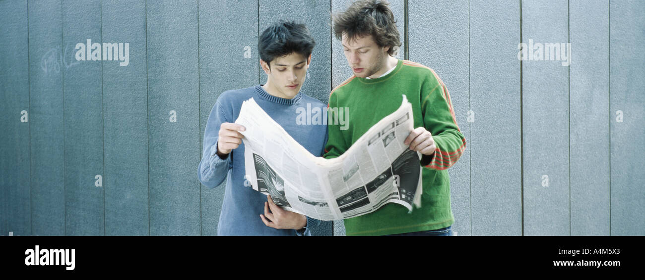 Two young men sharing newspaper - Stock Image