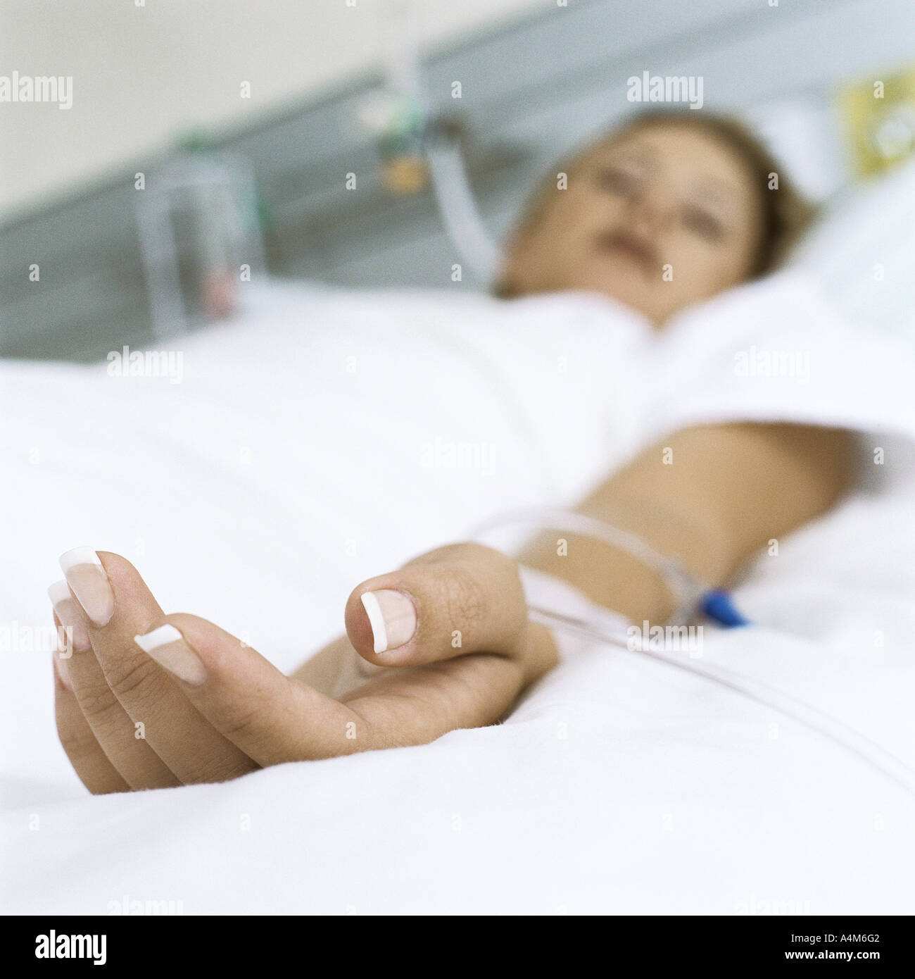Female patient lying in hospital bed - Stock Image