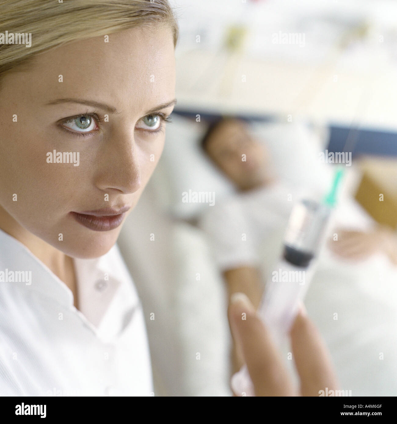 Nurse holding up syringe in front of patient Stock Photo