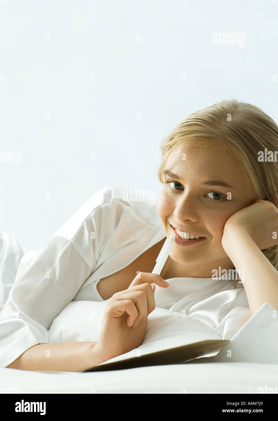 Young woman lying down with pen to lips - Stock Image