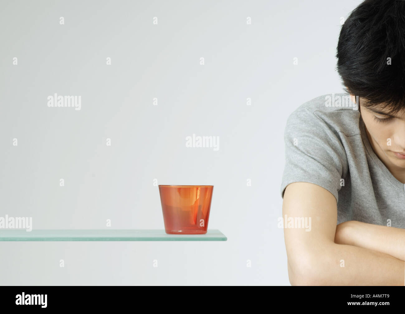 Young man with arms folded and head down - Stock Image