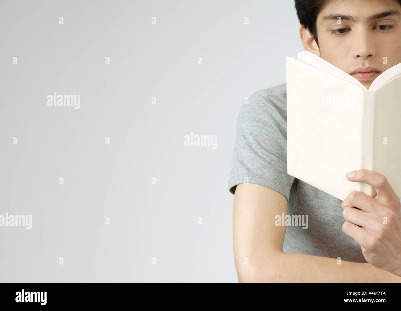Young man reading book, portrait - Stock Image