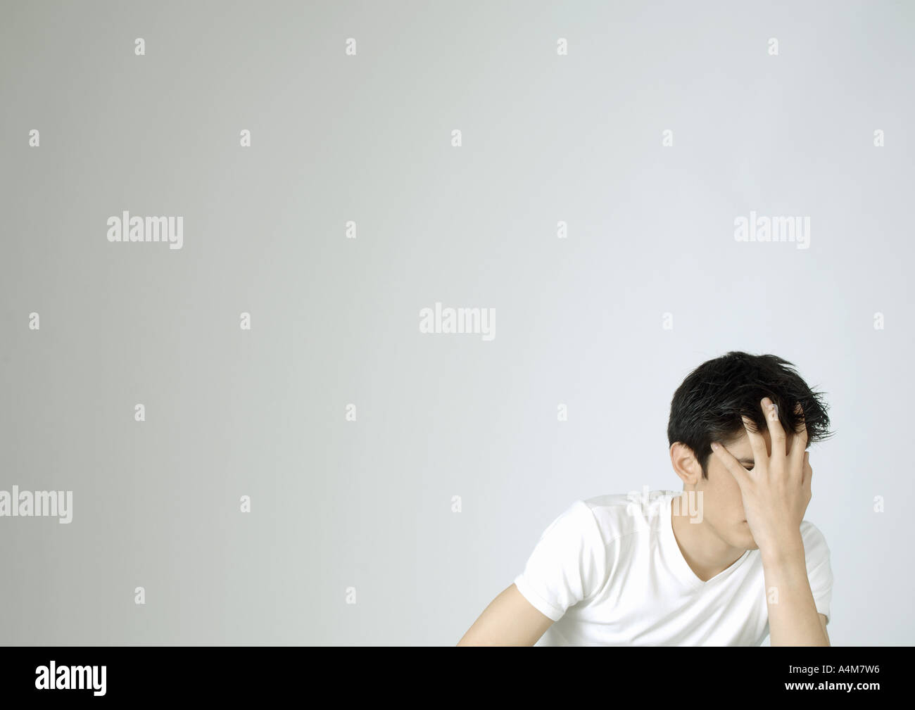 Young man covering face with hand - Stock Image