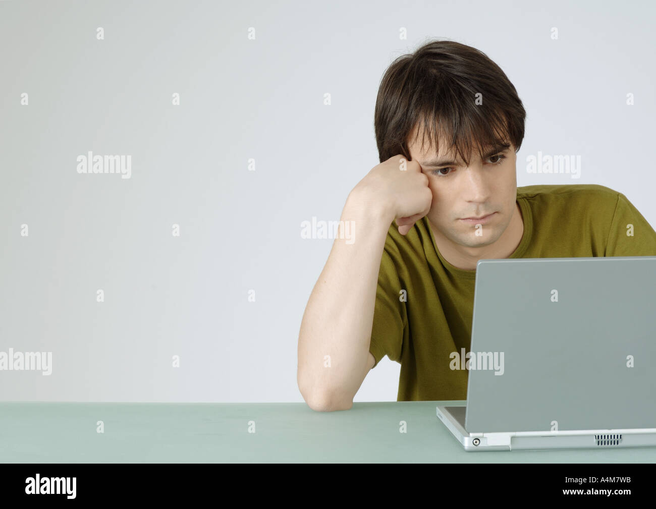 Young man using laptop, leaning on elbow - Stock Image