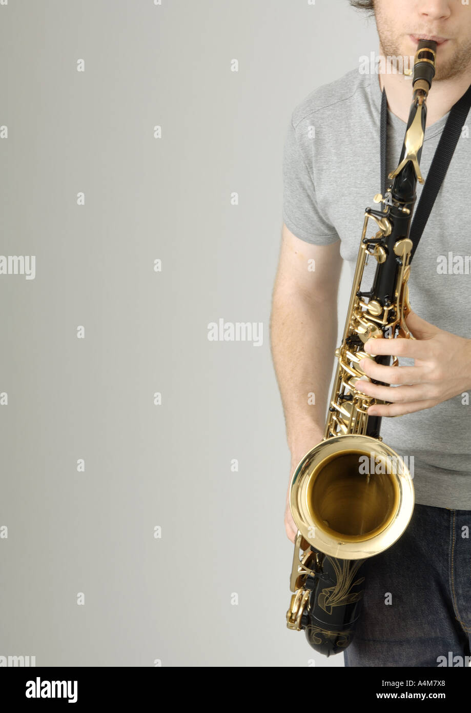 Young man playing saxophone, partial view - Stock Image