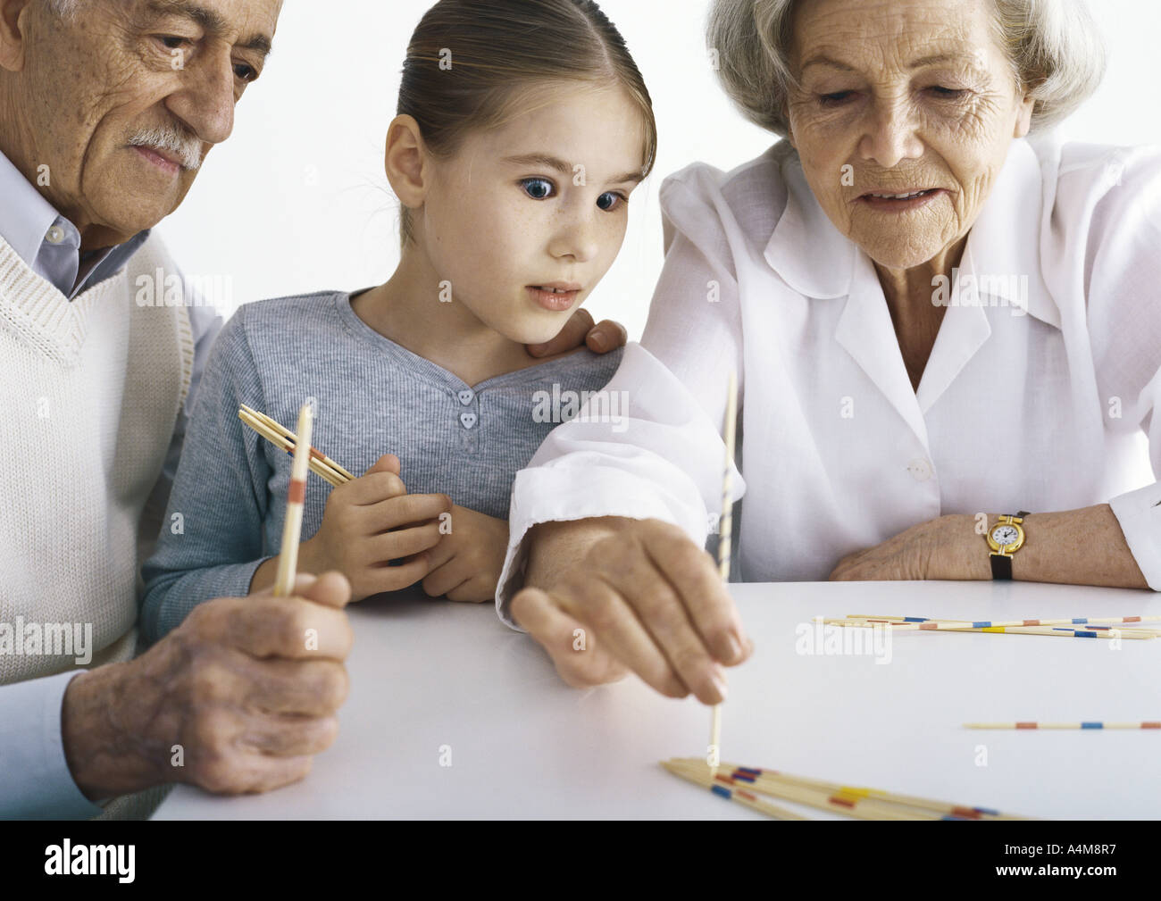 Grandparents and girl sitting at table playing pick up sticks Stock Photo