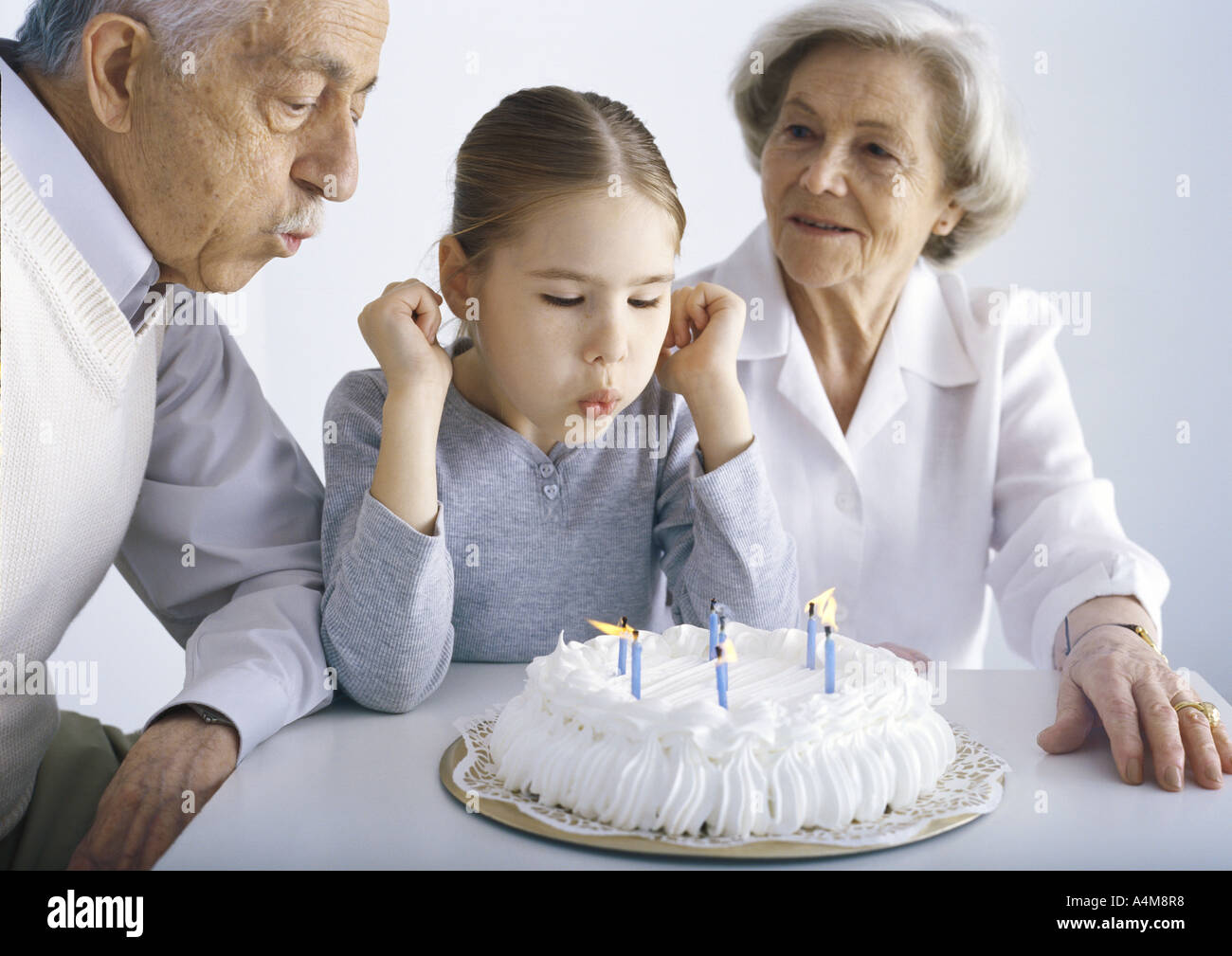 Girl sitting with grandparents, blowing out candles on cake Stock Photo