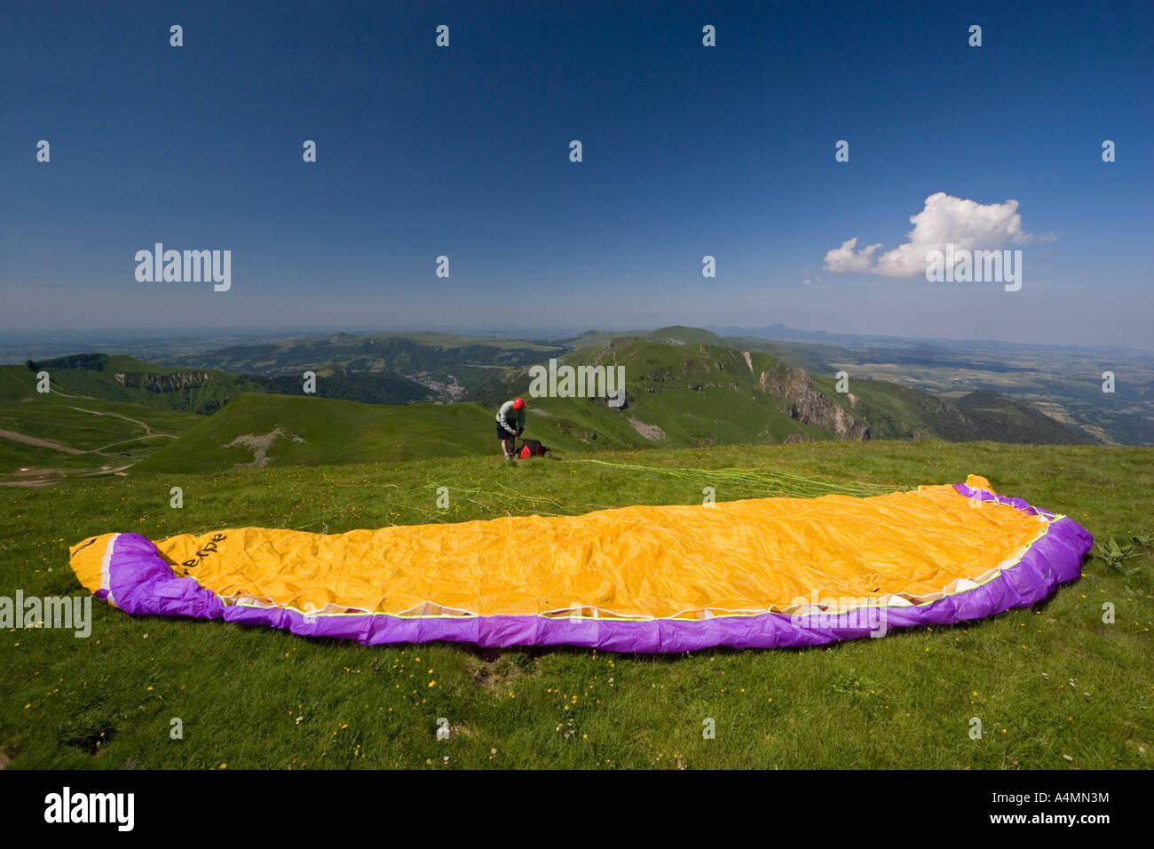 A paraglider preparing his takeoff over the Sancy Massif (France). Parapentiste préparant son envol dans le - Stock Image
