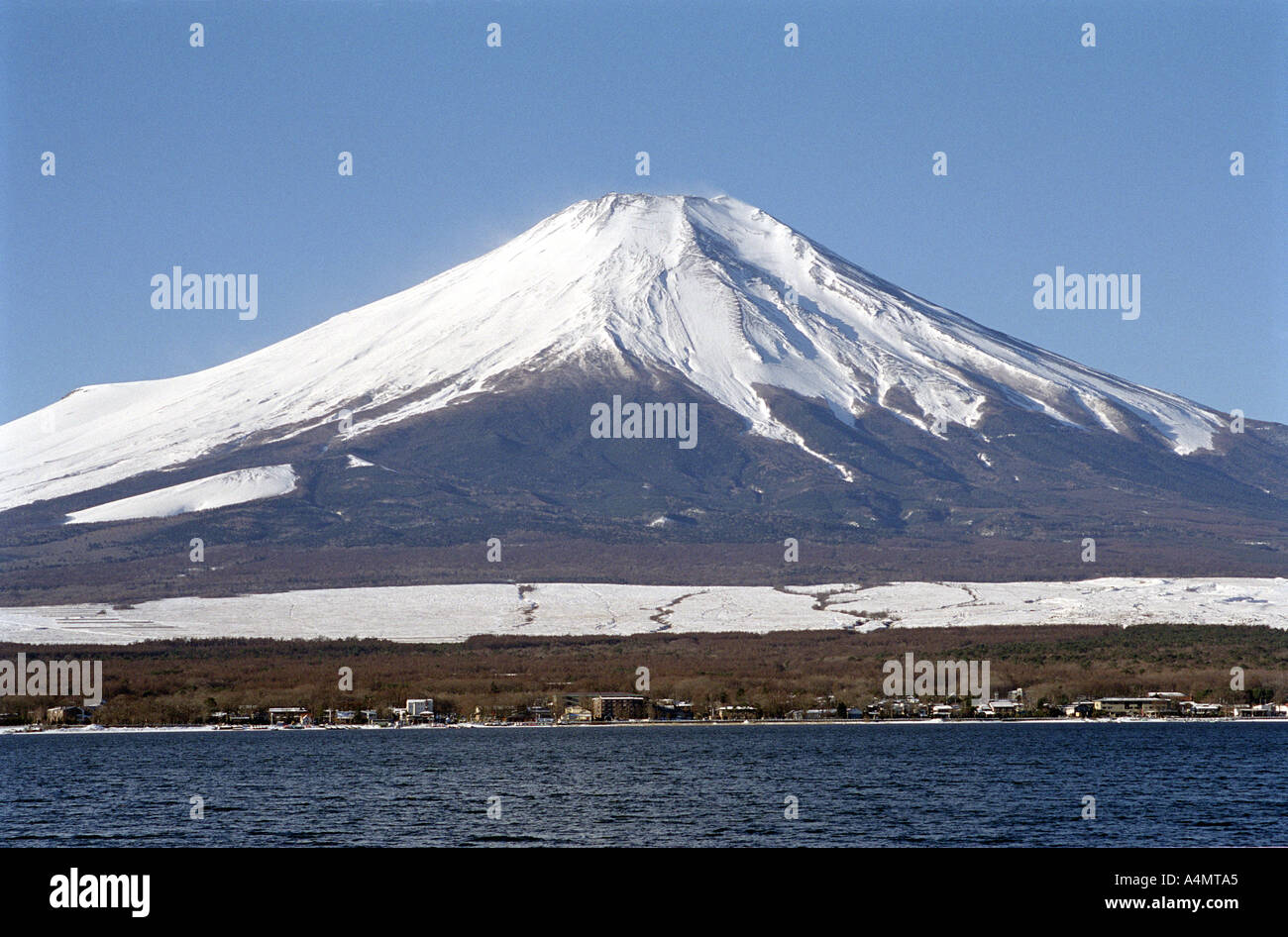 Snow capped Mount Fuji in Japan viewed in winter against a bright blue sky. - Stock Image