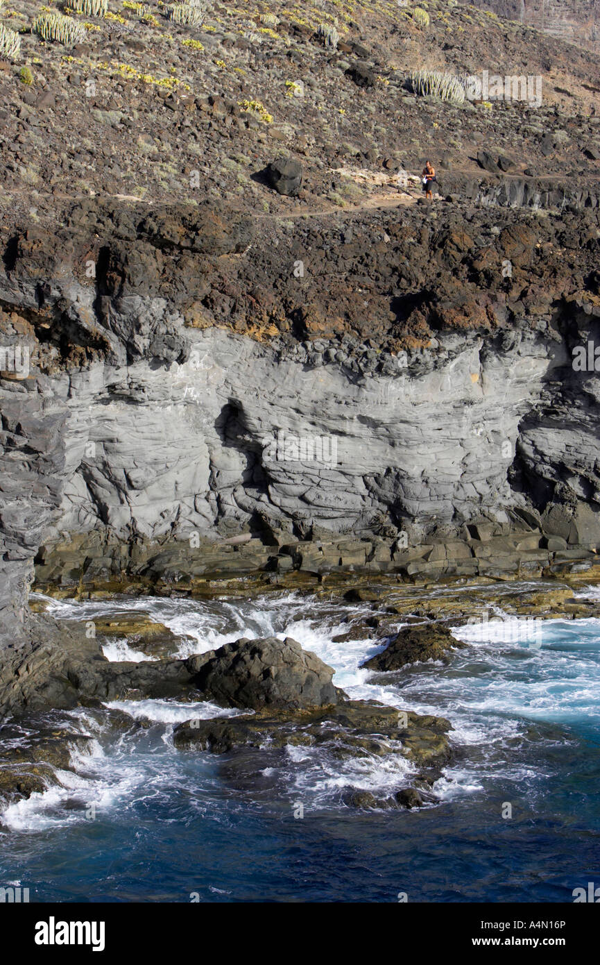 vertical man walking along rocky volcanic lava rock cliff formations on the coast at punta de teno Tenerife Canary Stock Photo