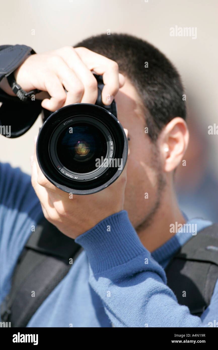 young man pointing canon camera with 24 70mm 2 8 L lens at camera taking a photograph - Stock Image