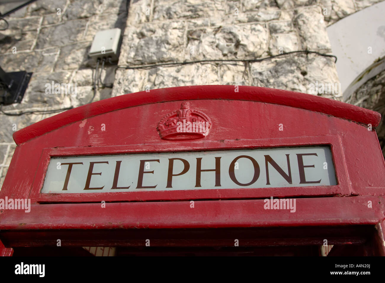 top of old style red telephone box with crown detail in Carnlough county antrim white limestone bridge in the background - Stock Image