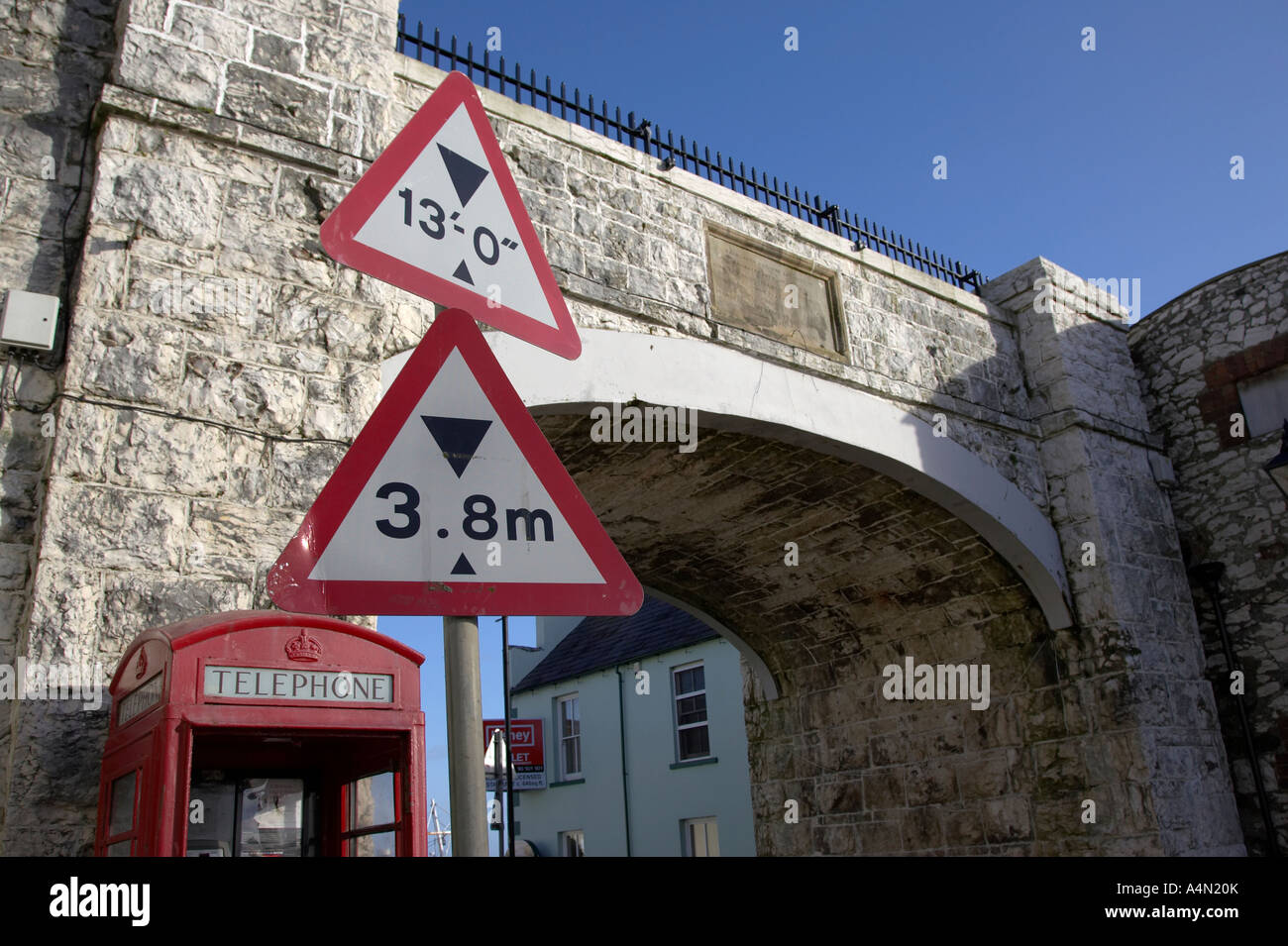 red triangular height warning signs in front of white limestone bridge and red telephone box in Carnlough county - Stock Image