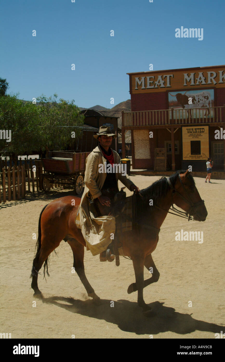 Cowboy On A Horse Riding Through A Wild West Film Set Town In Stock Photo Alamy