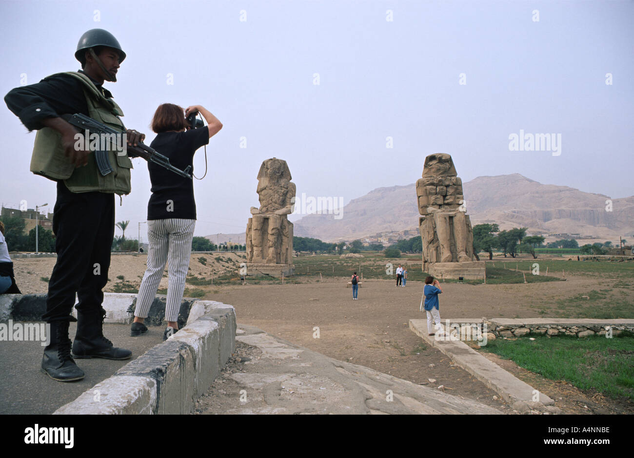 Tourists take snapshots under close guard of an Egyptian soldier at the Collossi of Memnon Stock Photo