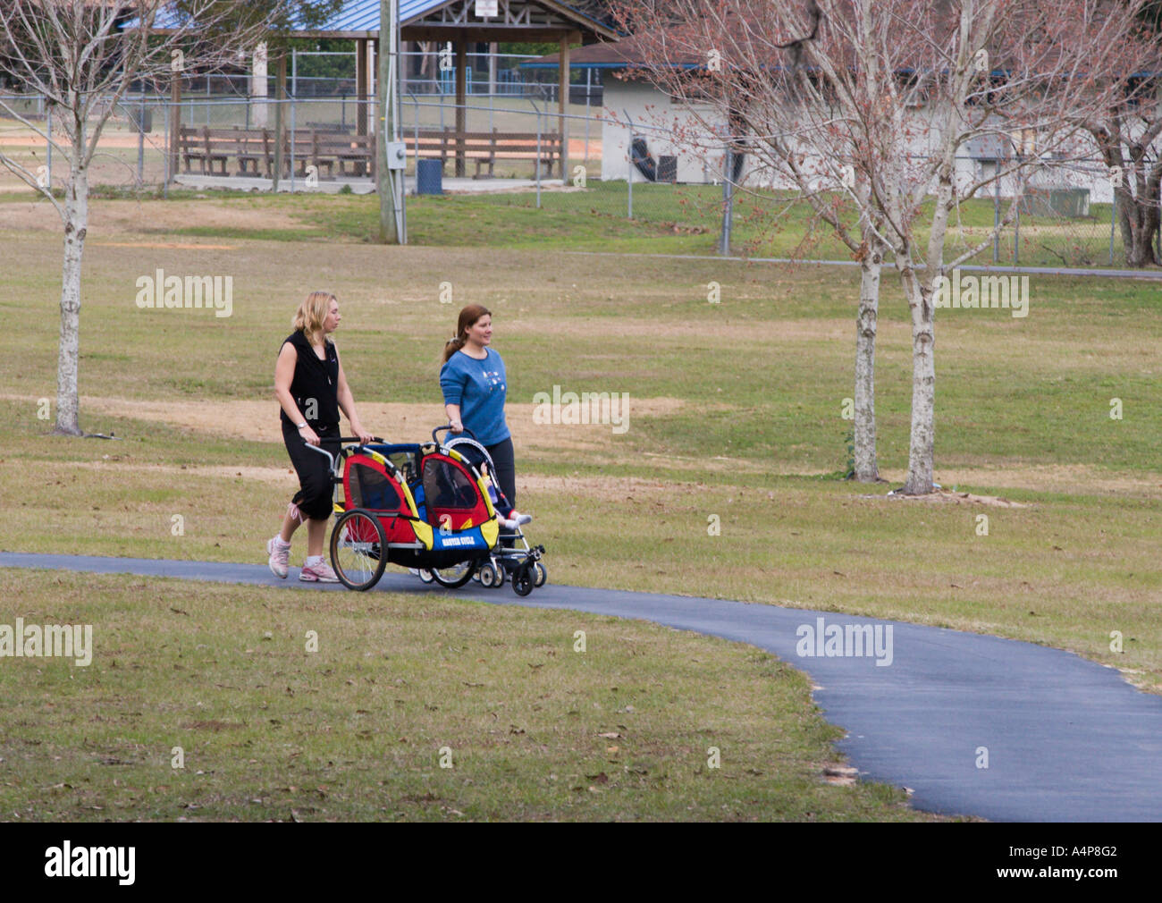 Two women walking and pushing babies in strollers through Jervey Gannt Park in Ocala Florida USA Stock Photo