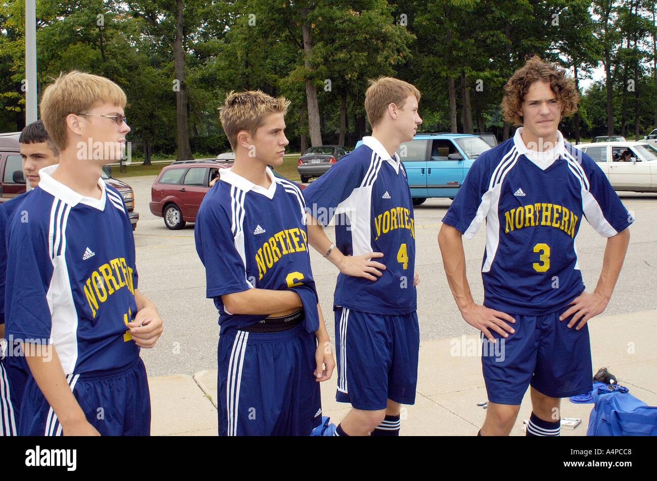 Soccer players stand around talking with each other - Stock Image