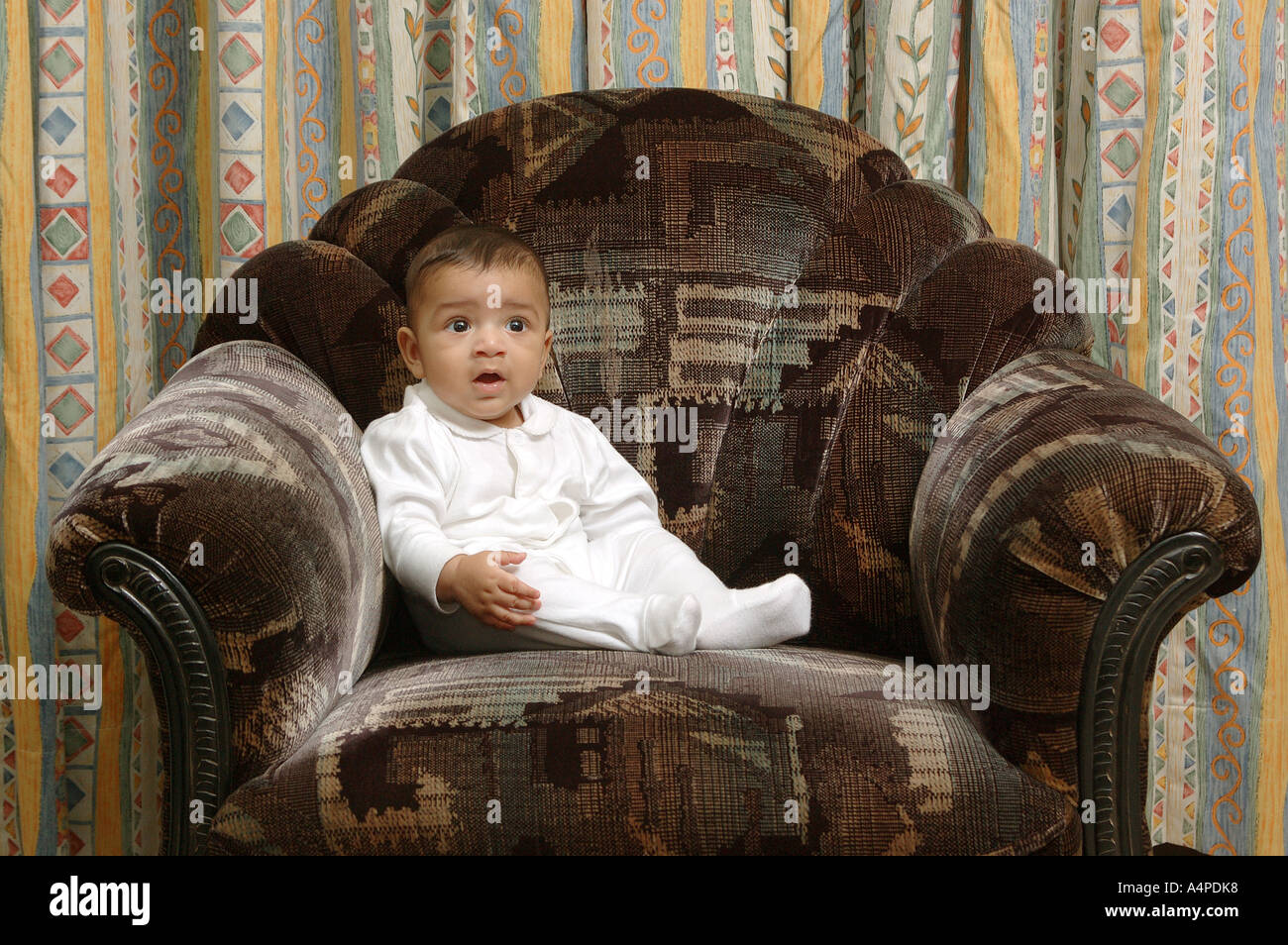 Ang77653 Young Indian Boy Four Months Old Sitting On Sofa Chair Like