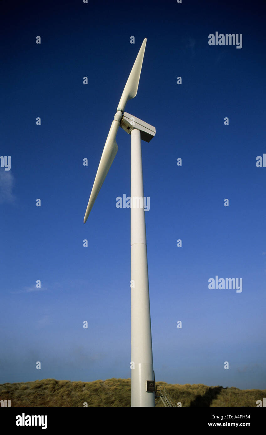 A white two bladed wind turbine against a clear blue sky. Near the coast in The Netherlands. - Stock Image