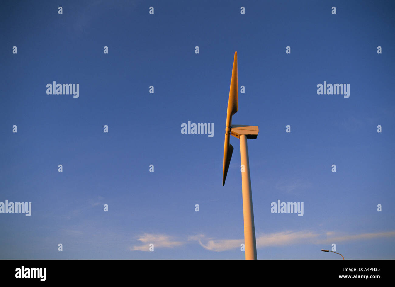 A two bladed wind turbine against a clear blue sky at sunset. Near the coast in The Netherlands. - Stock Image