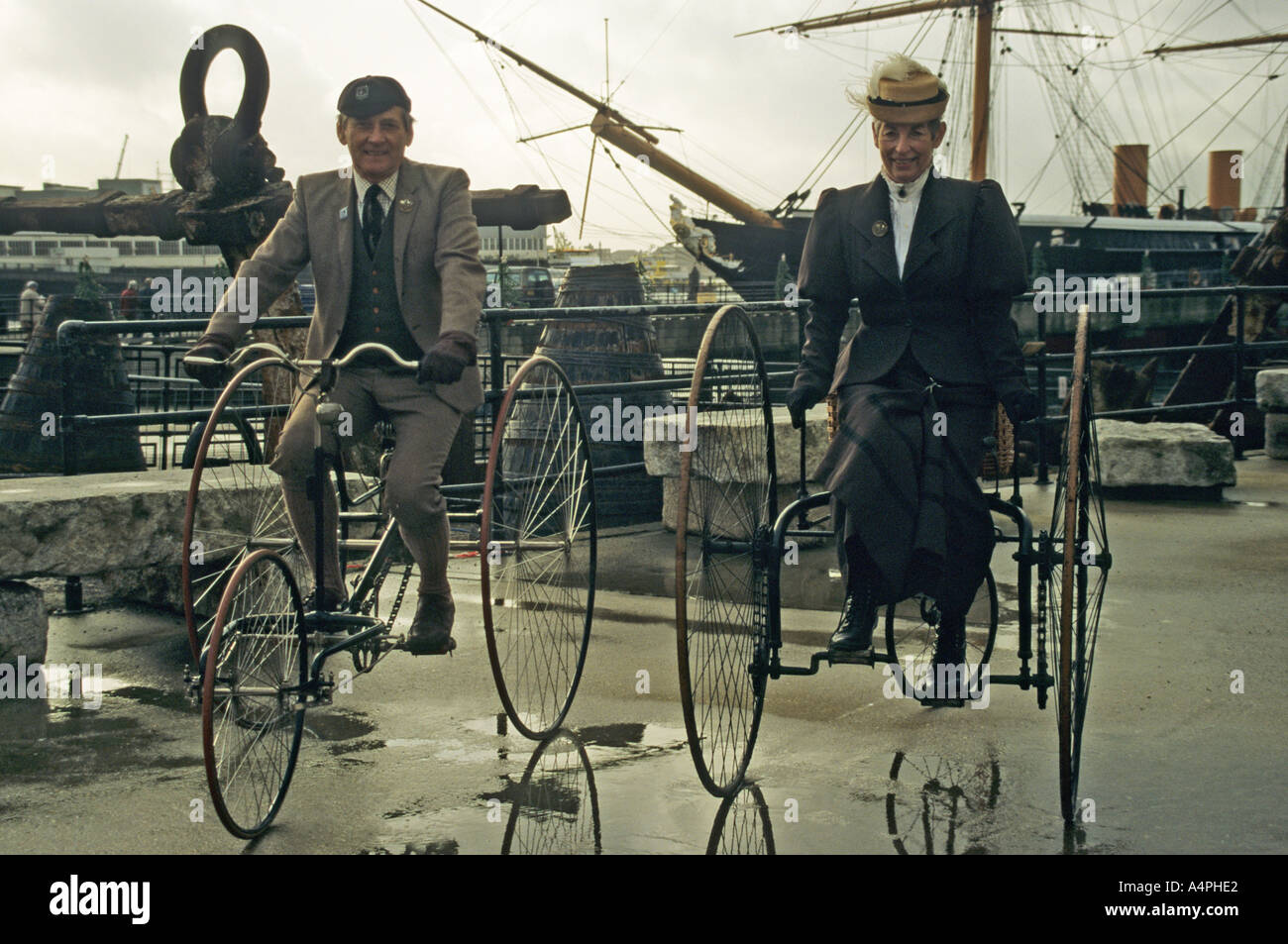 elderly woman and gentleman riding old fashioned bicycles re enactment in Portsmouth Docks Hampshire - Stock Image