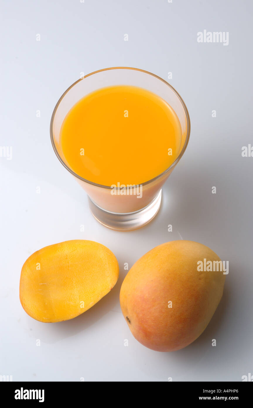 44158205 ANG77741 Mango fruit juice in glass, one piece of cut and one full uncut  ripe mango