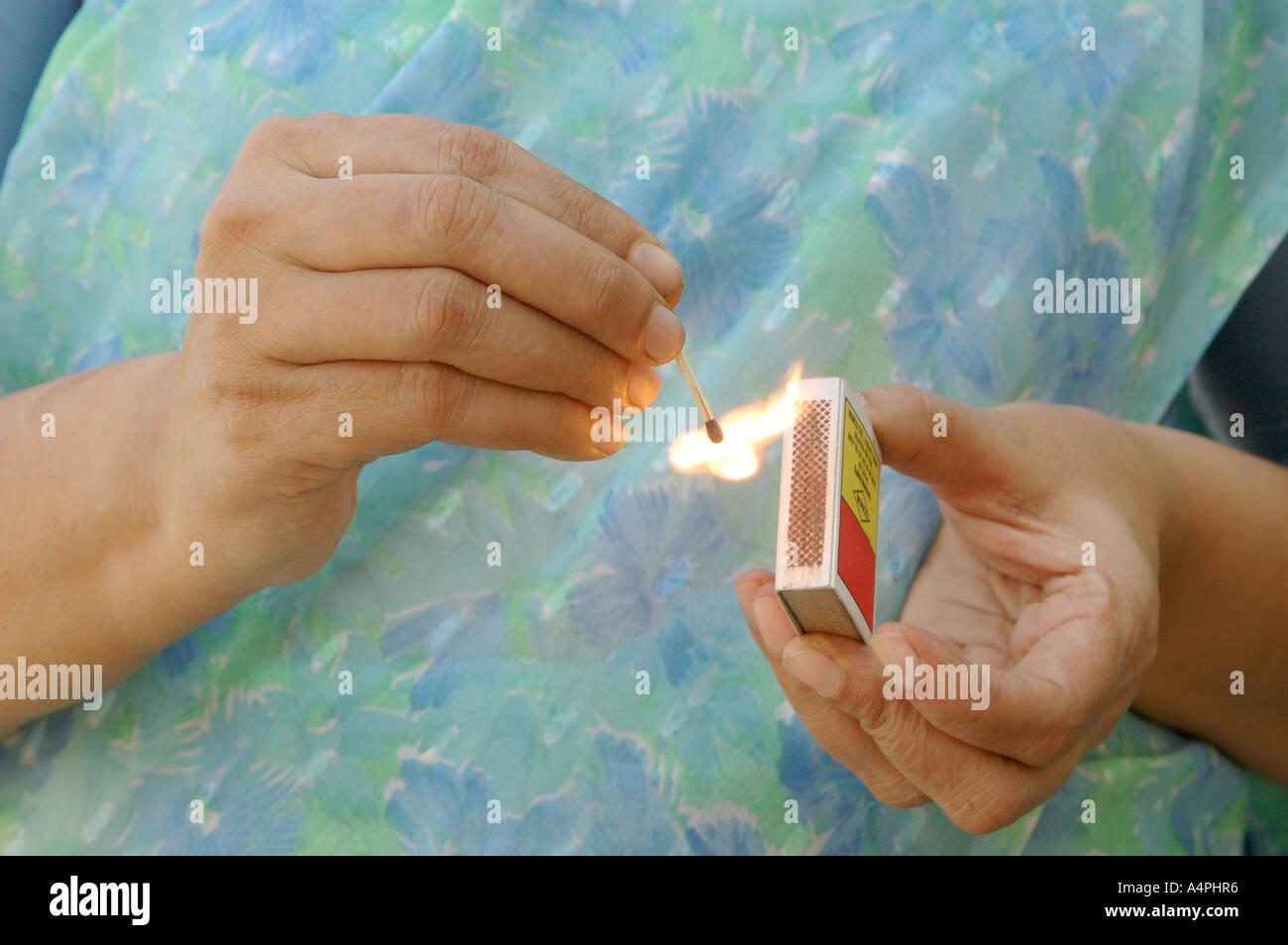 ANG77747 Lighting a match stick by rubbing hard by women on match box - Stock Image