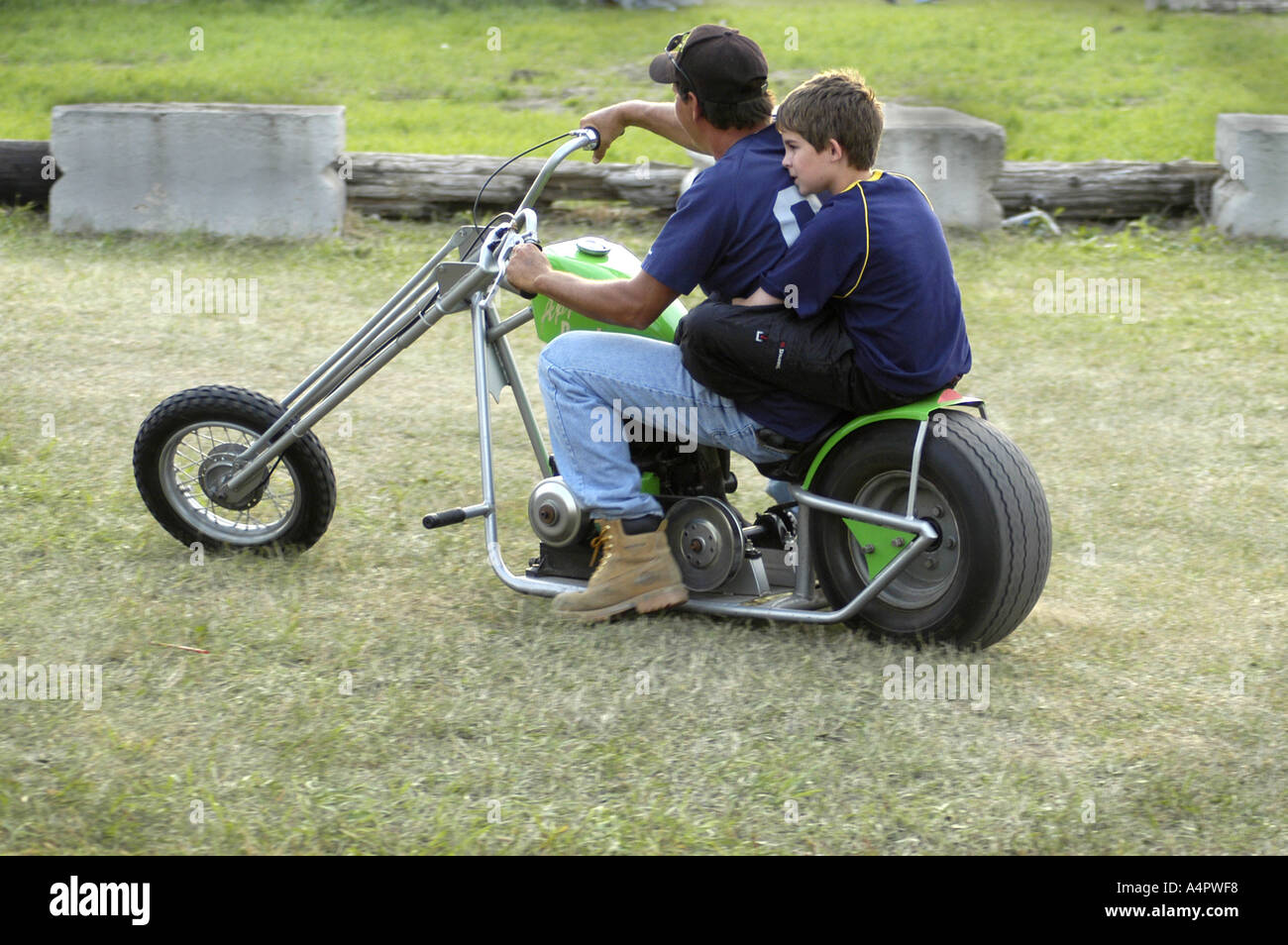 Dad and son in pits on chopper mini bike at dirt track motorcycle race Croswell Michigan USA - Stock Image