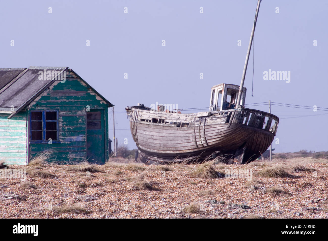 Abandoned wooden fishing boat next to a dilapidated green hut on the shingle beach at  Dungeness in Kent. Stock Photo