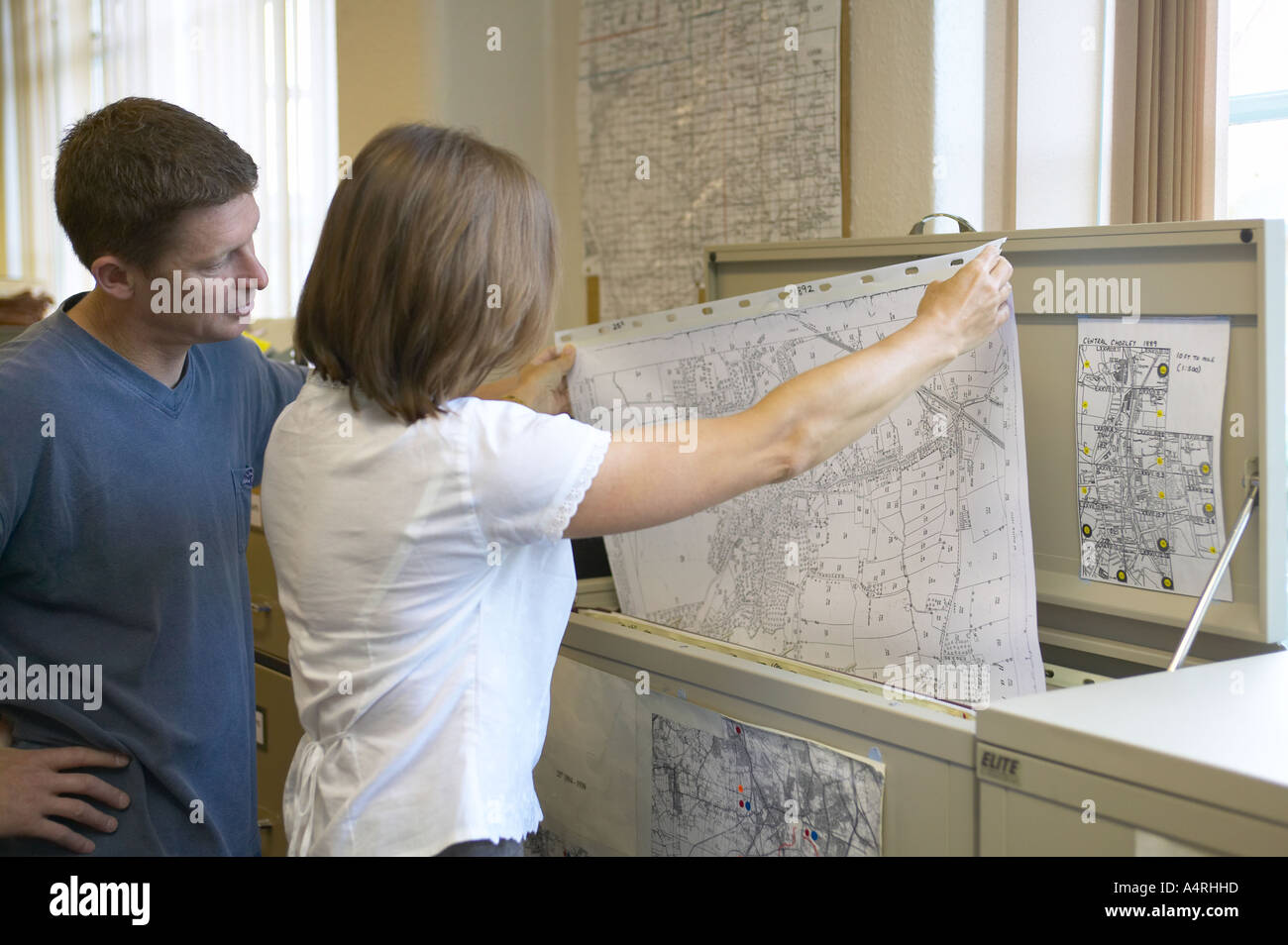 librarian helping a customer lift a map from the reference cabinet file - Stock Image