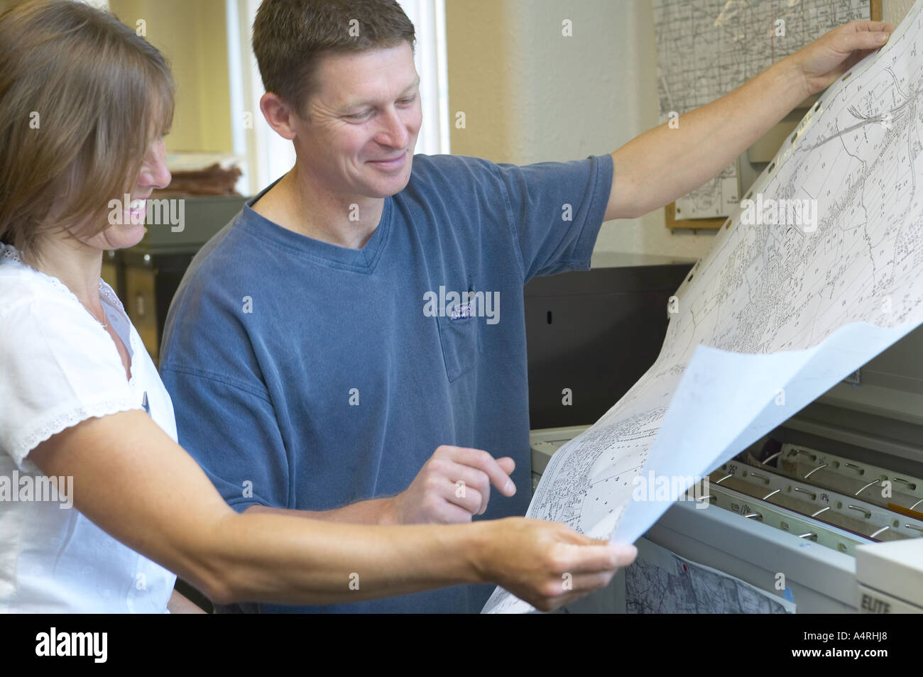 librarian helping a customer study a map from the reference archive - Stock Image