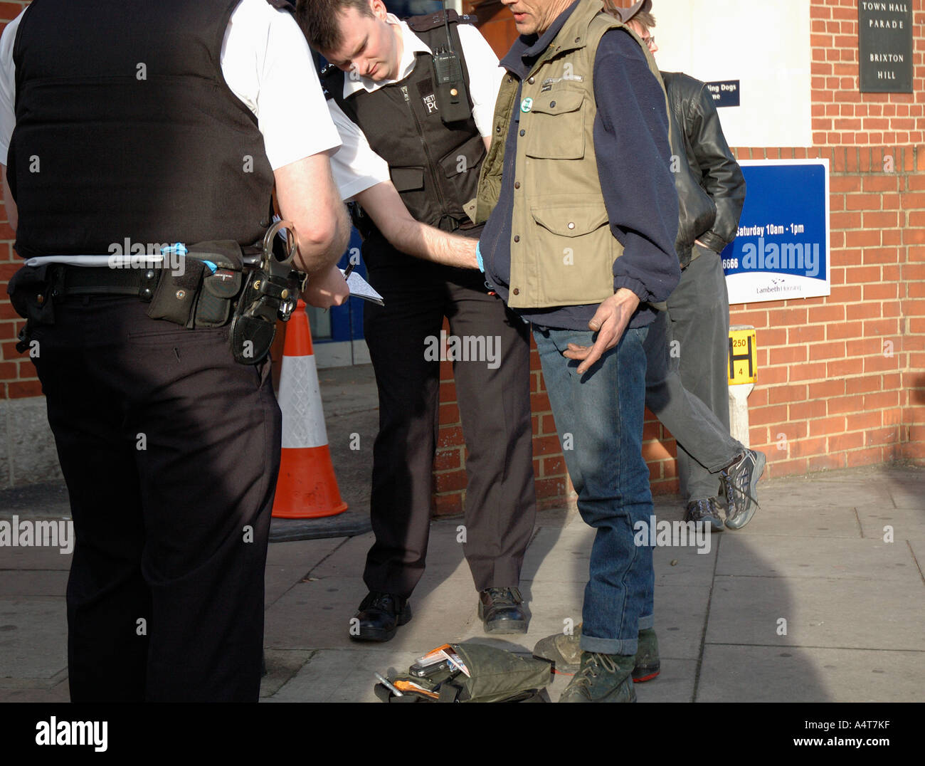 Police stop and searching youth in the streets of Brixton. - Stock Image