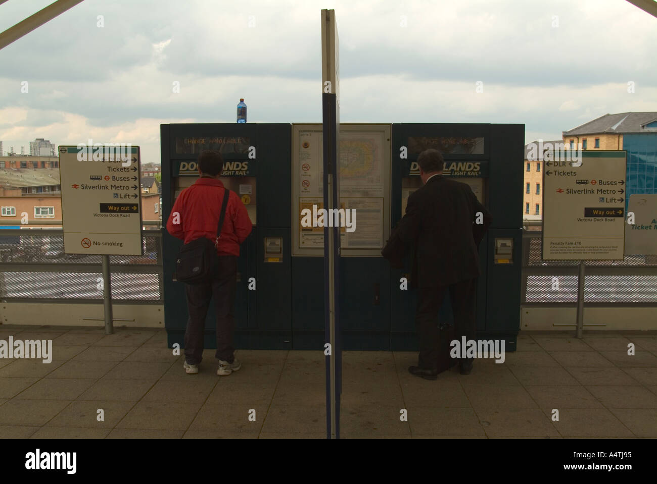 Passengers buying train tickets from automated machine on station platform Docklands London UK Stock Photo