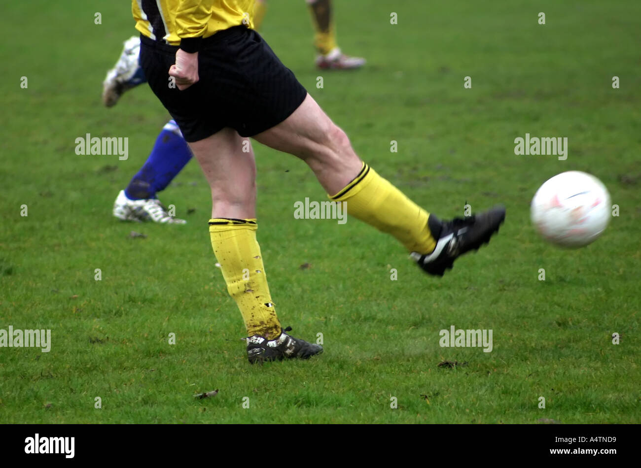 Footballer kicking a ball - Stock Image
