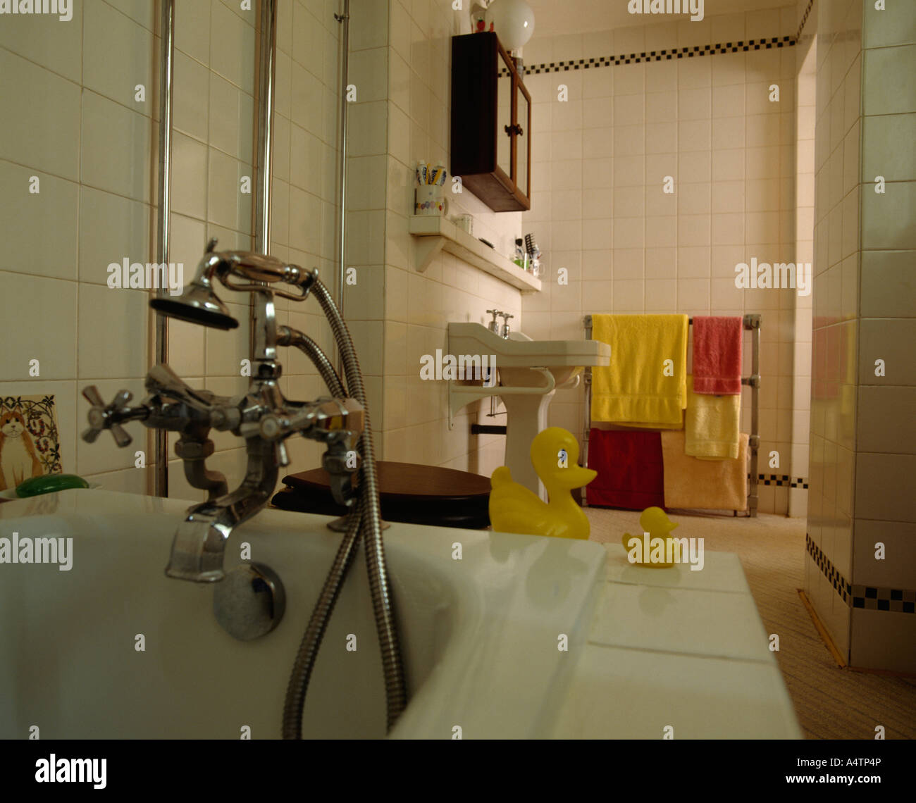 Bath with shower attachment and taps and yellow plastic ducks on ...